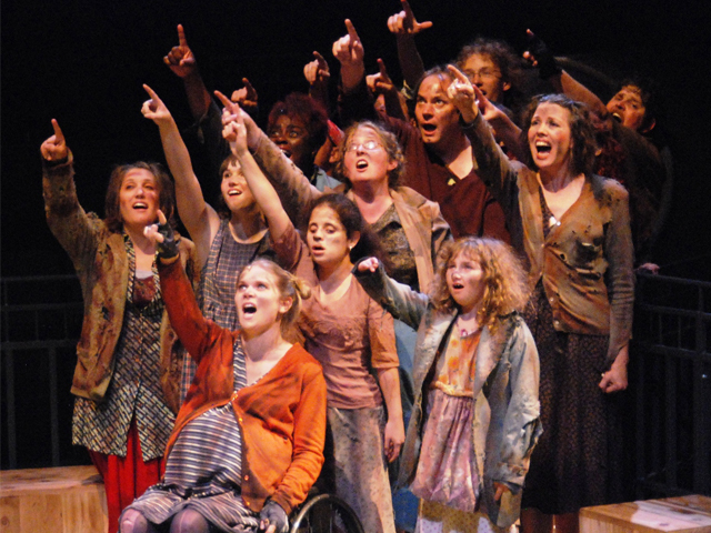 Photo from urinetown with all cast gathered and pointing upward