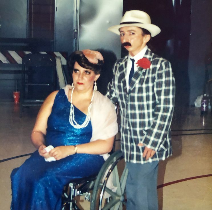 Woman in wheelchair and blue dress from the 20s, man standing behind in checkered suit and mustache.