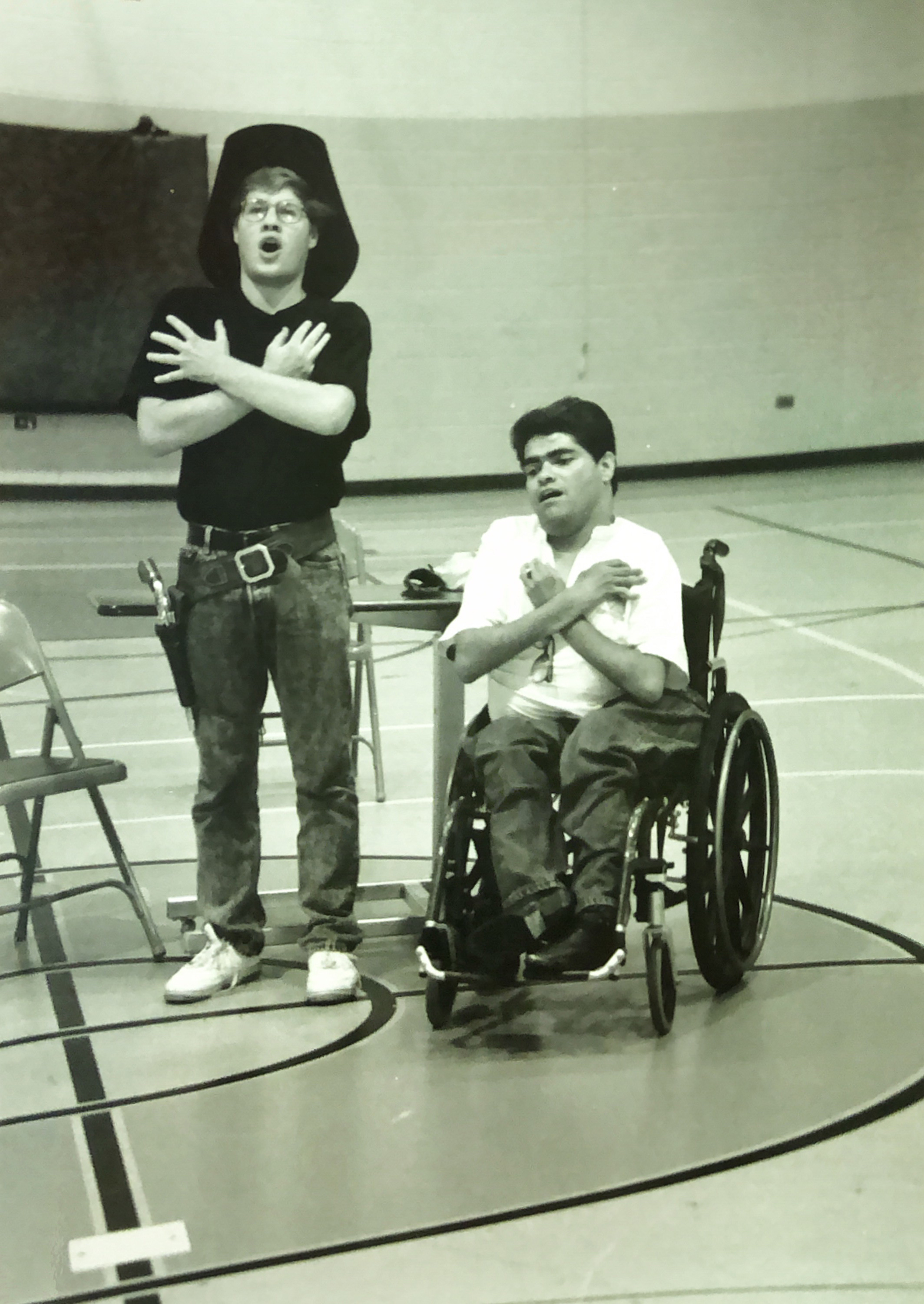 Black and white photo of two men, one in a wheelchair both with their arms crossed over their chest