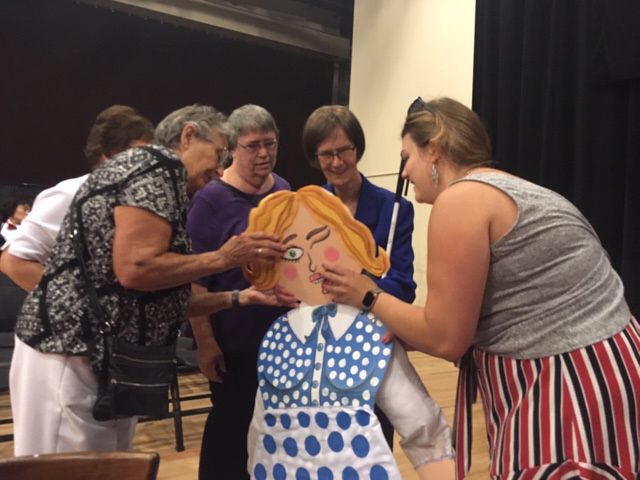 Four blind women surrounding a puppet and touching it.