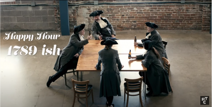 """Photo of five individuals gathered around a table drinking. They are dressed in colonial suits and hats. What text reads """"Happy Hour 1789ish"""""""