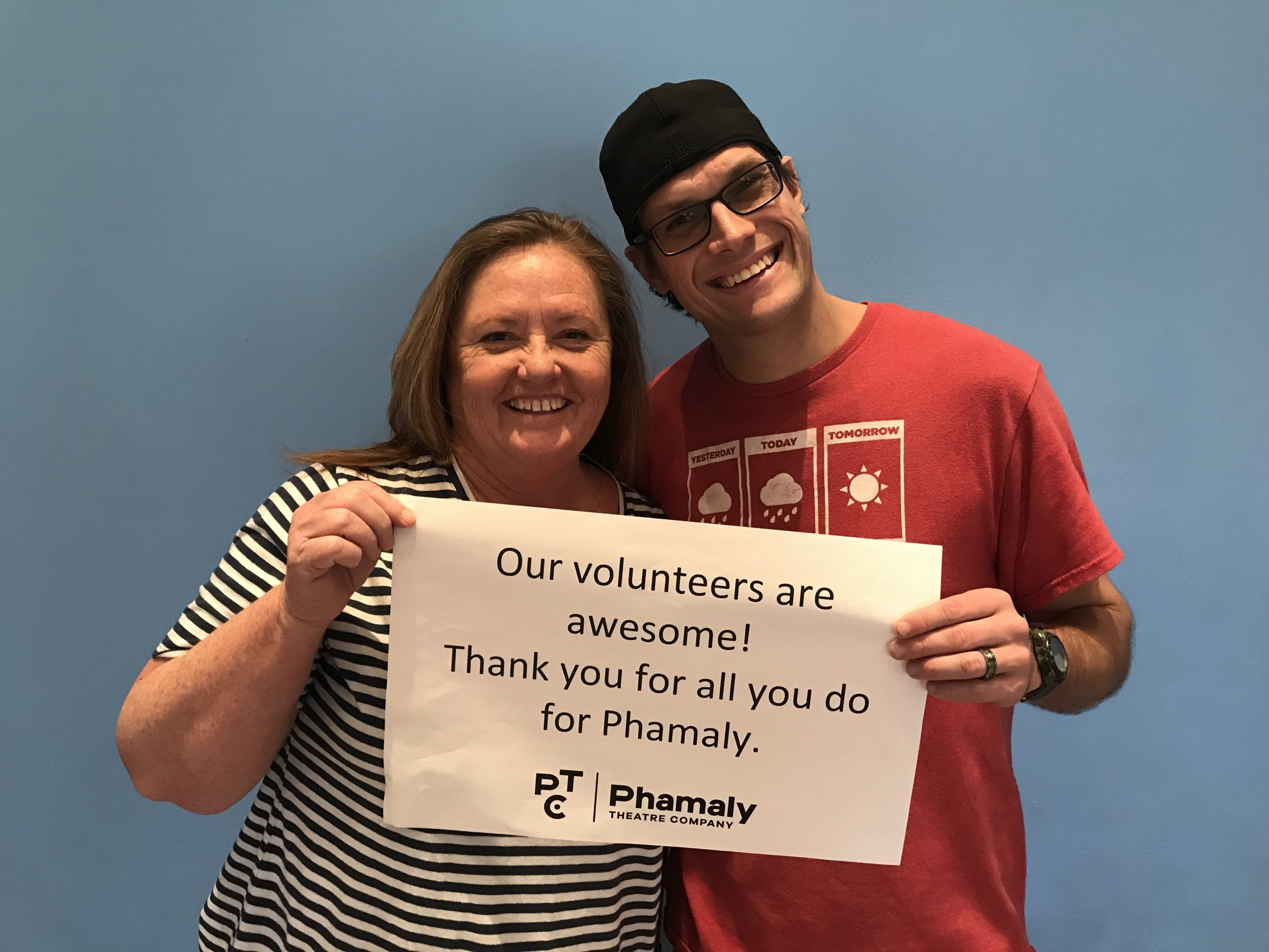 "Two Volunteers holding a sign that reads ""Our volunteers are awesome! Thank you for all you do for Phamaly"""