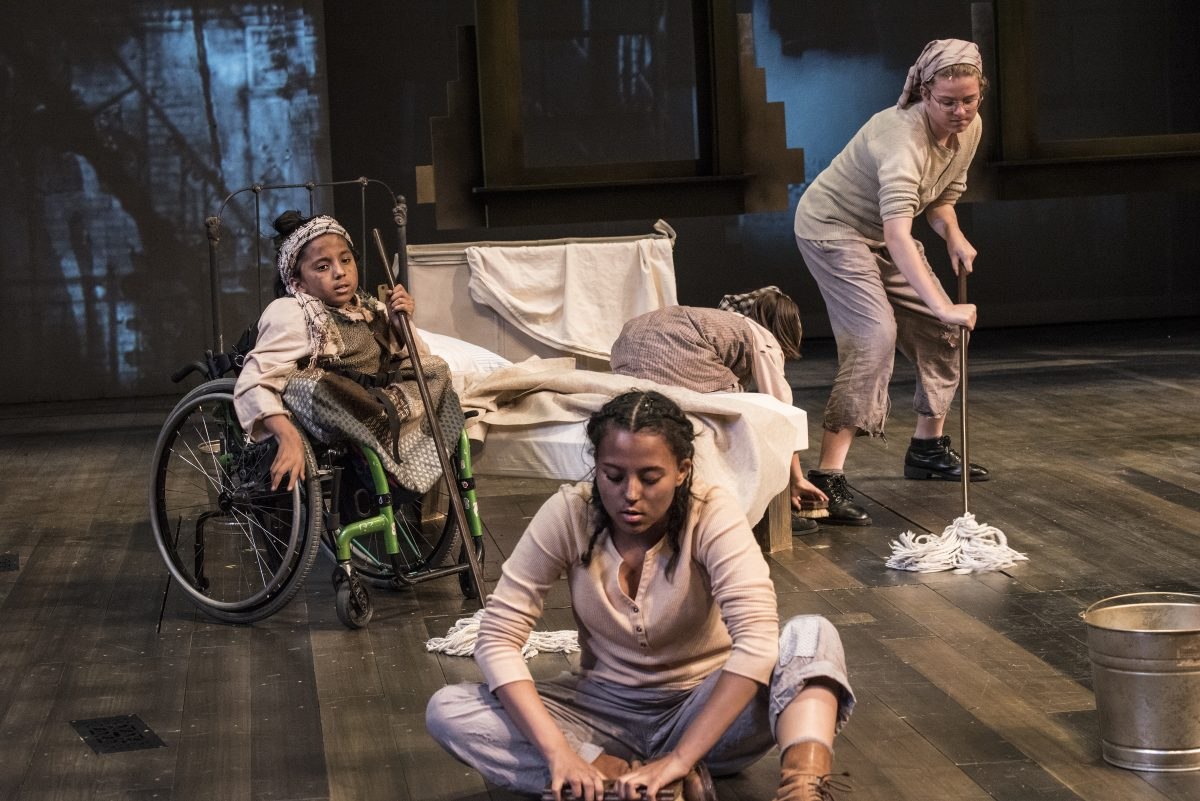 Three young girls in underclothes cleaning, one is in wheelchair