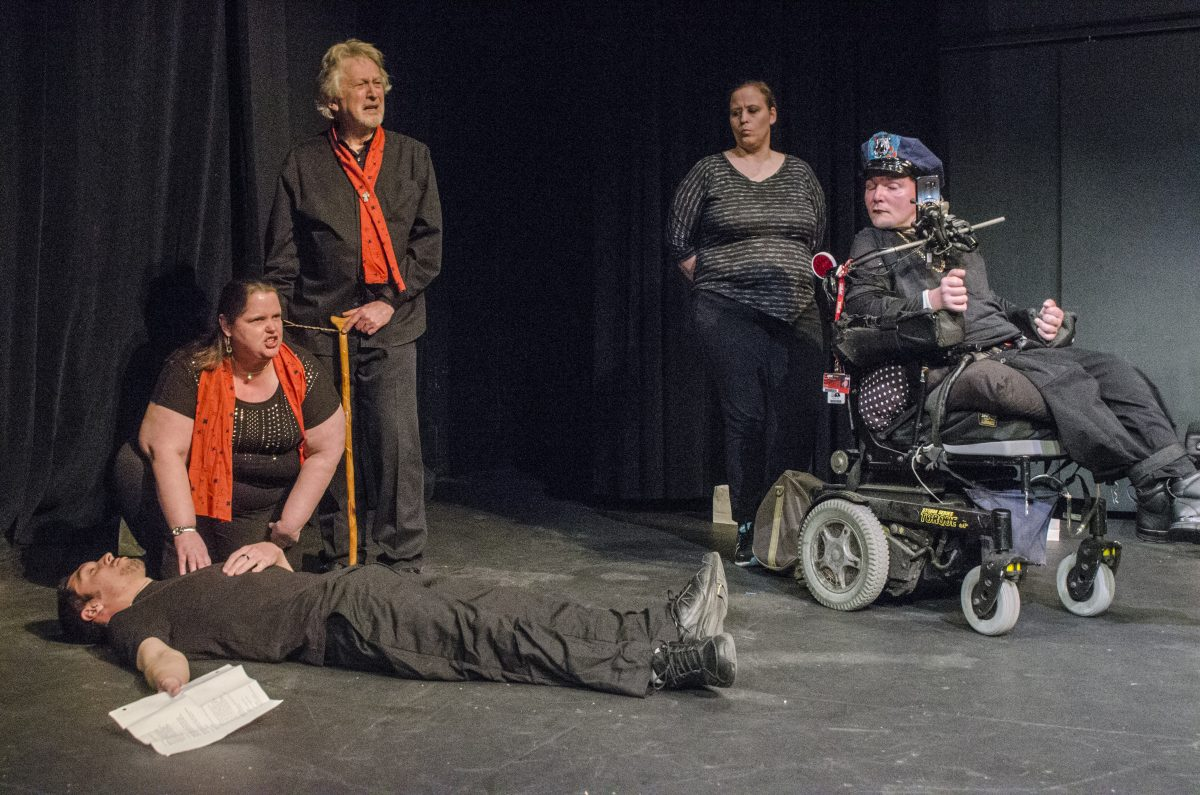Man lying on floor with Woman in red scarf kneeling beside. Man with red scarf and cane standing behind and two others, one in a wheelchair, off to the right.