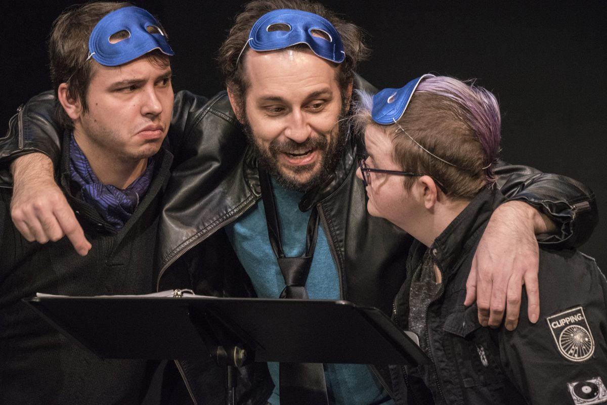 Three younger men in huddle, all wearing blue masks on their foreheads.