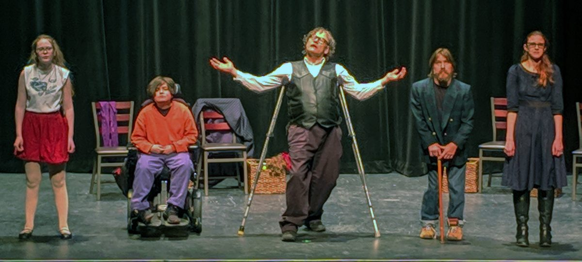 FIve actors, one of whom is in a wheelchair and another on crutches and one with a walker facing the audience.