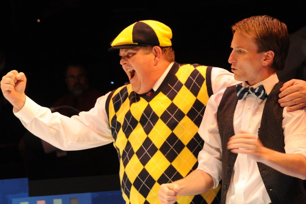 A man in yellow golf attire adding emphasis of line with fist out and his arm around a man in business casual reacting nervously