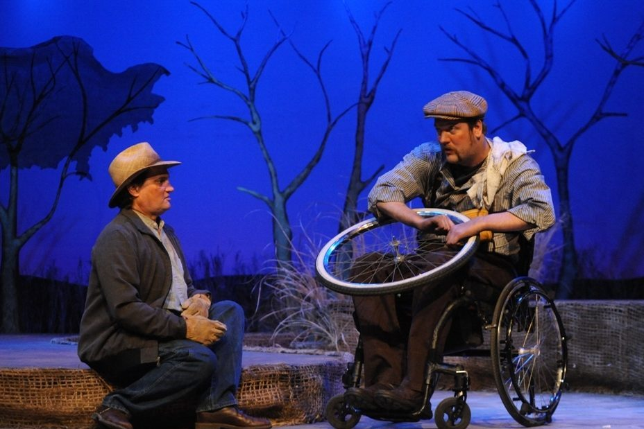 A man in a cowboy hat sitting with a man in a wheelchair who is cleaning a wheel