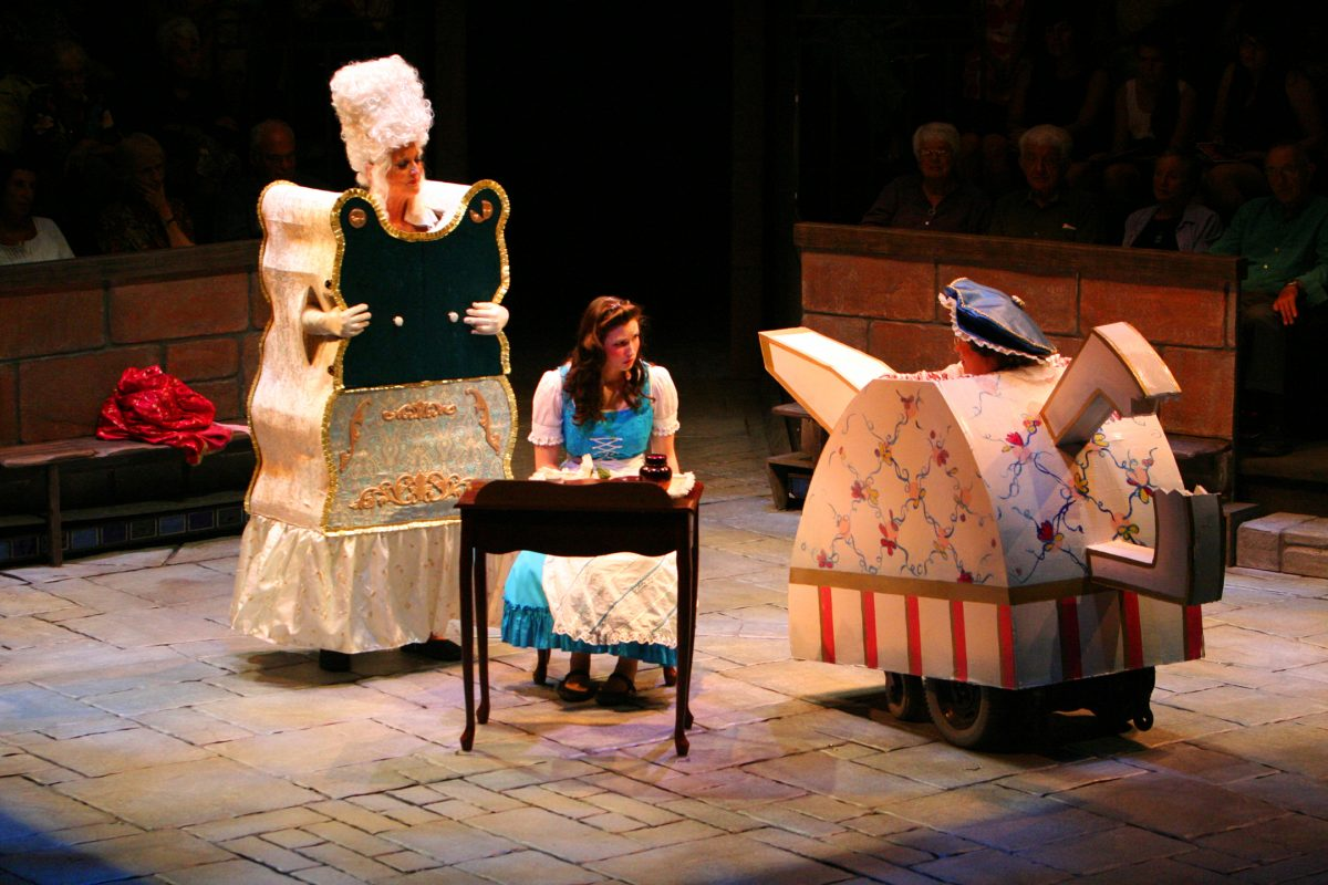 A woman dressed as a wardrobe and a woman dressed as a tea pot giving a girl advice