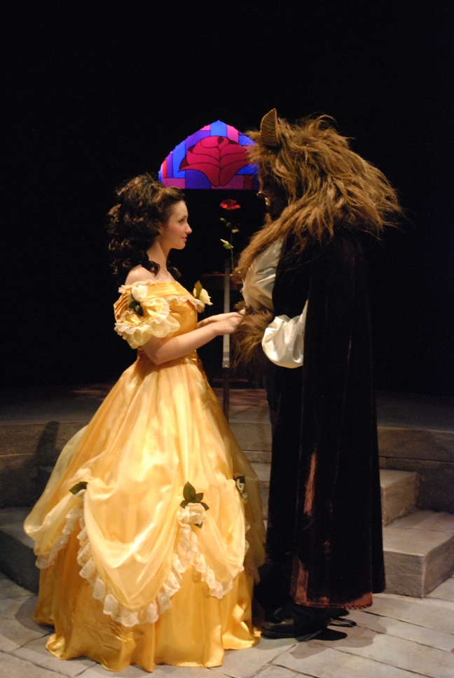 A woman in a gold ball gown with a beast made up of brown fur in a suit