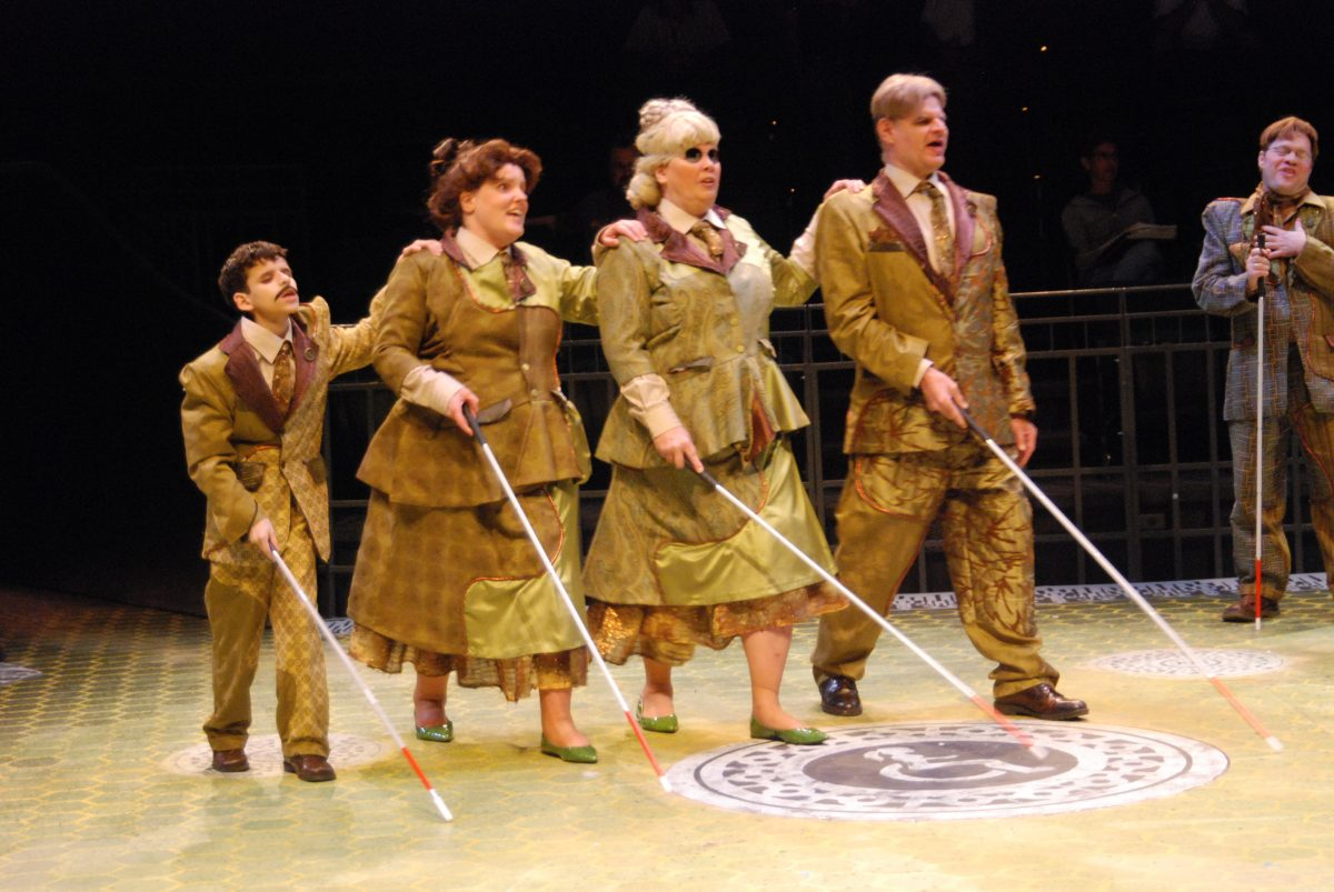 Four people in a line of ascending height and pea green uniforms, each with their left hand on the shoulders of the person next to them and a white cane. Fifth man standing off to the side with a white cane.