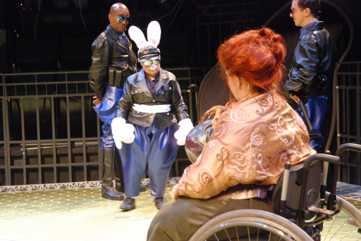 Man in police uniform and sunglasses with woman in police uniform with bunny ears and oversized white gloves facing woman with red hair in a wheelchair whose back is to the camera..
