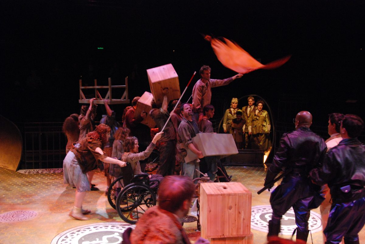 Group of people creating a barricade, one person waving a red flag. Group of people in the background in pea green uniforms watching.