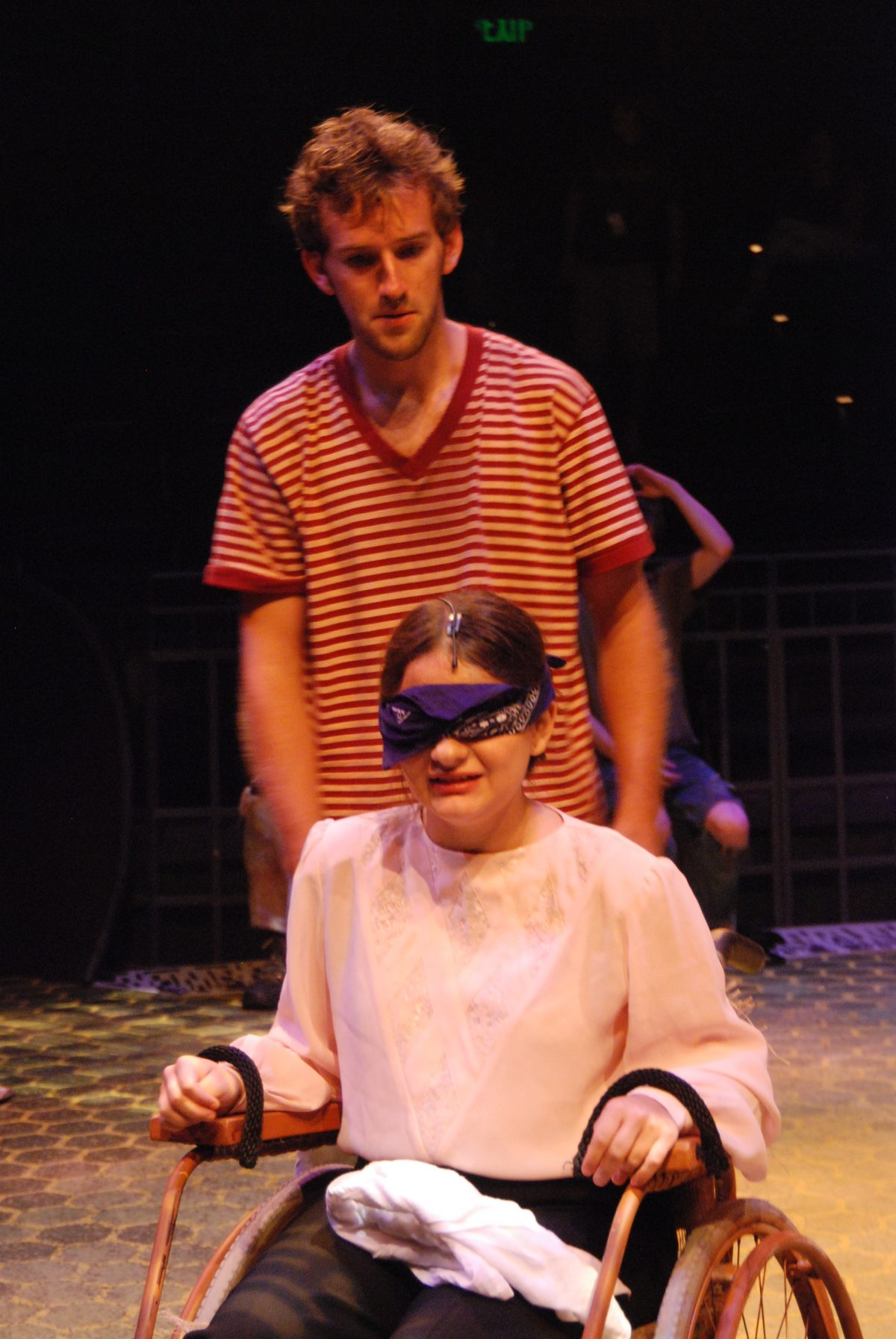Young man in dirty clothes standing behind a blindfolded girl who is tied to a wheelchair.