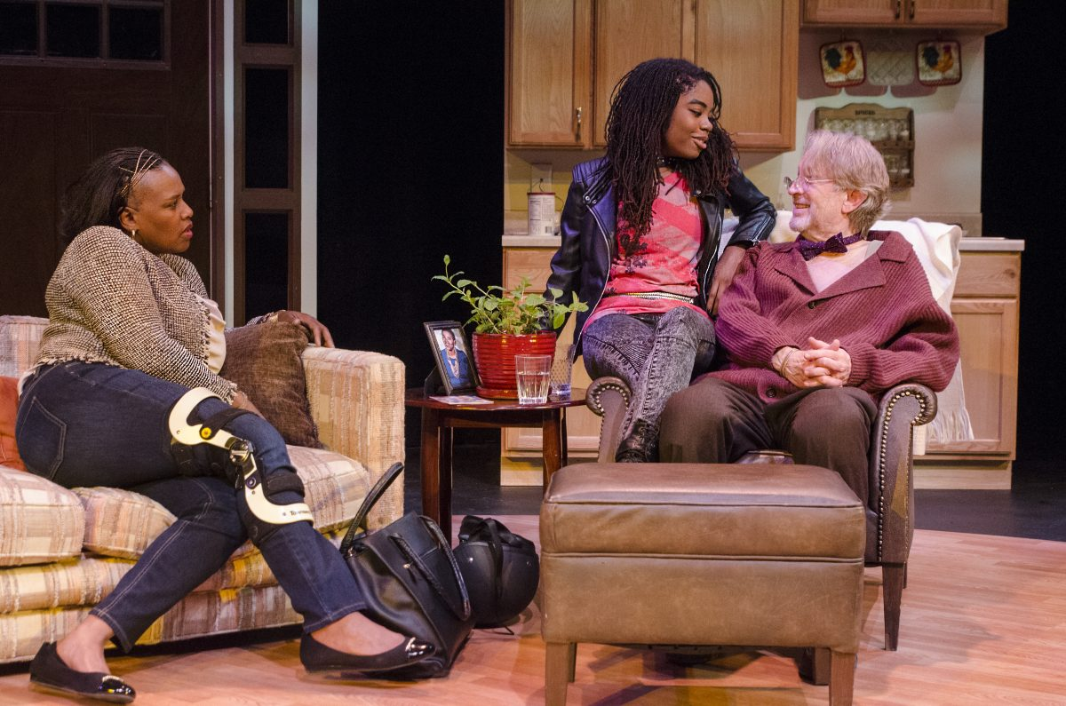 Black woman with leg braces sitting on couch, Older white man with bow tie and pajama top and in chair with young black girl sitting on the arm of the chair.