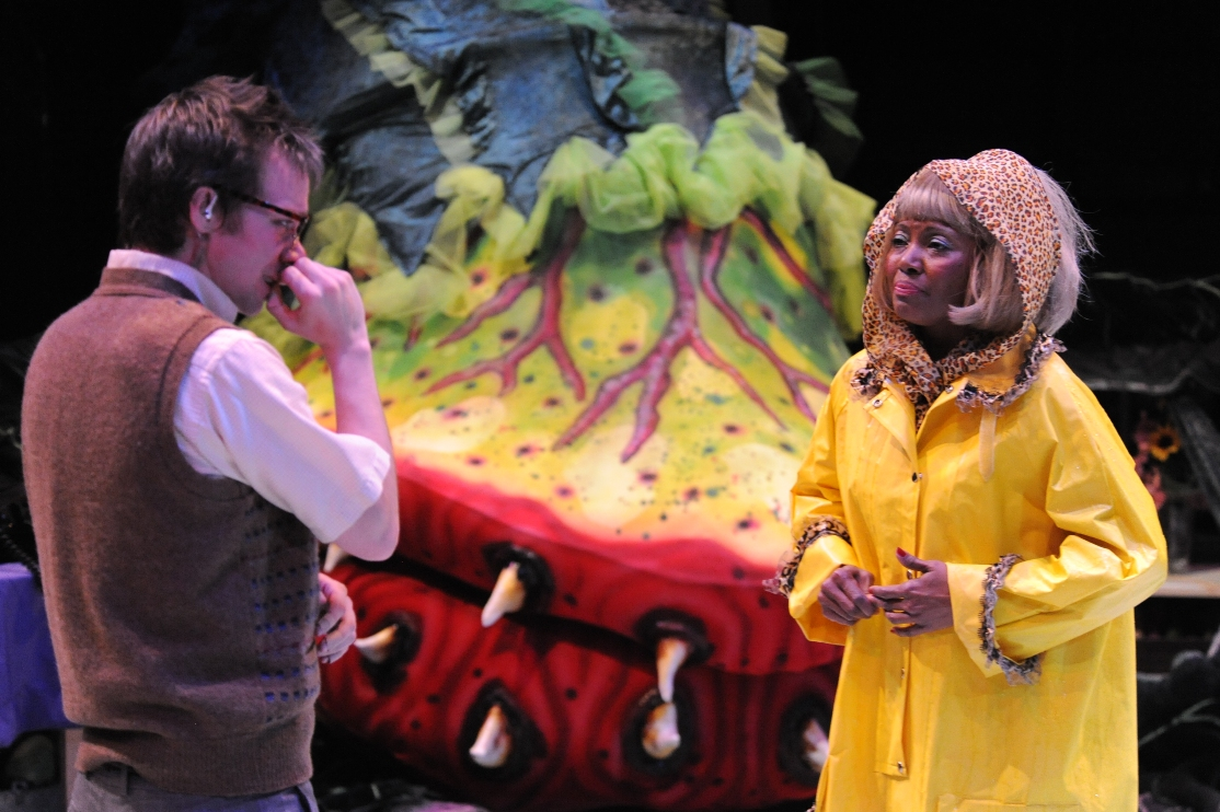 A man dressed as a nerd with a woman in a yellow rain coat and a larger than life yellow plant with teeth behind them.