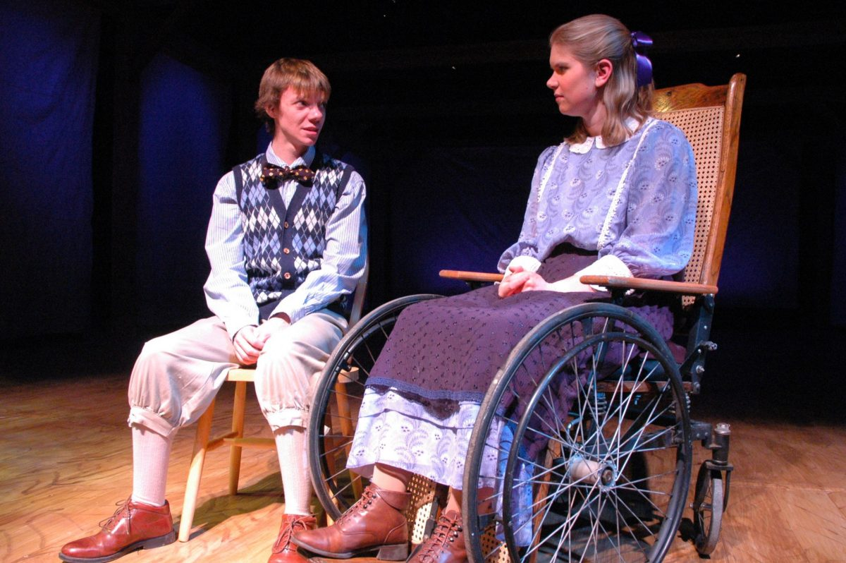 Boy with bowtie sitting next to a girl in a wheelchair.