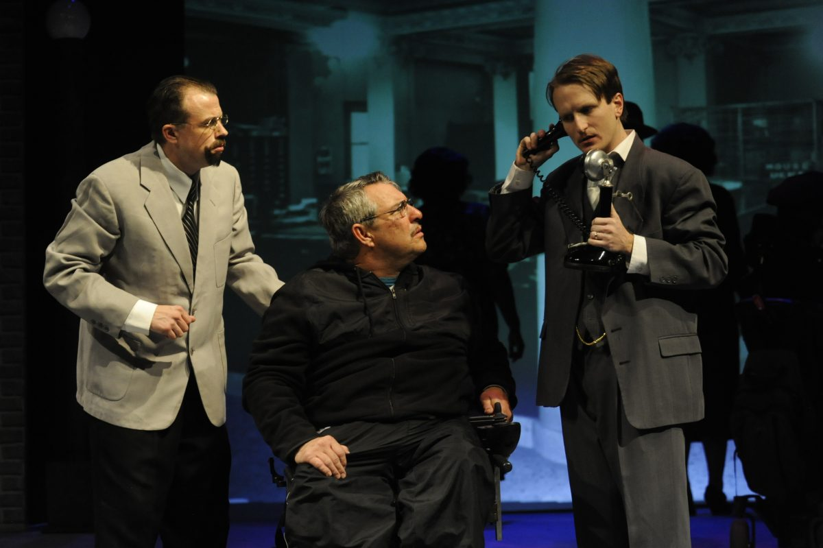 Two men in suits, one in a wheelchair looking at a third man who is on a old time phone.