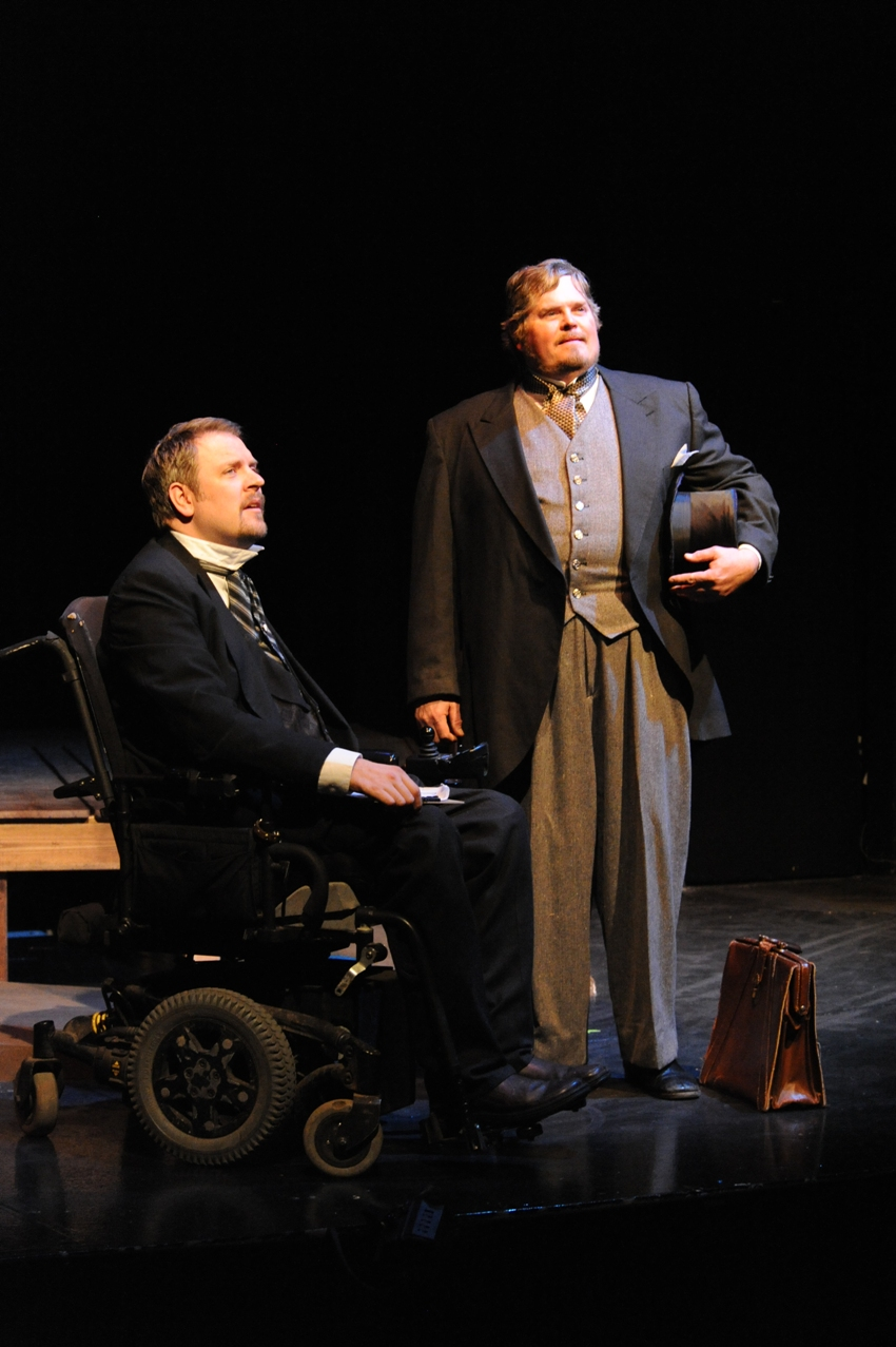 Man in dark suit and wheelchair beside man in gray suit holding a tophat.