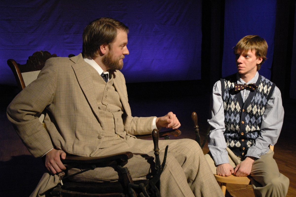 Man in the three piece suit and bowtie sitting and talking to a boy in an argyle vest and bowtie.