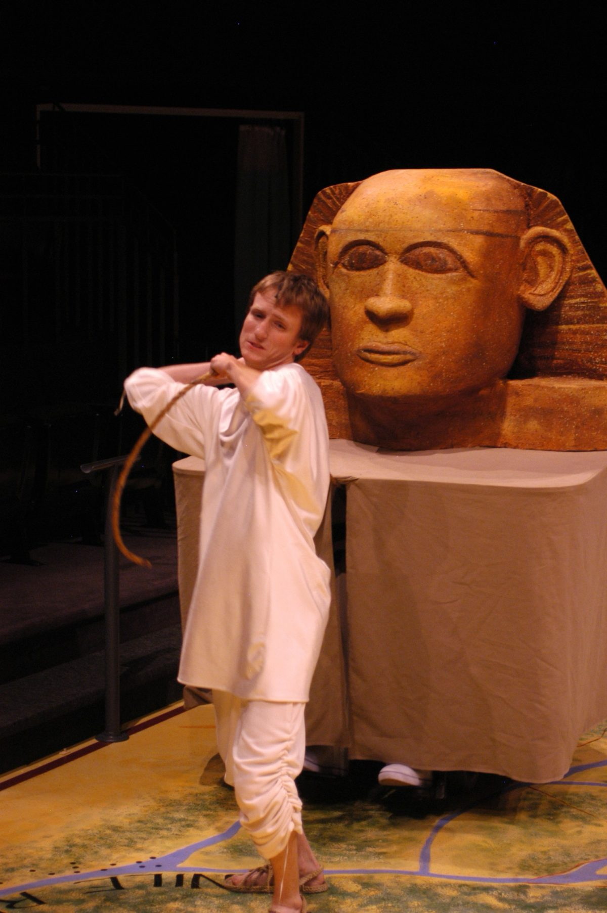 Man in plain white robes pulling a rope attached to a large sculpted head.