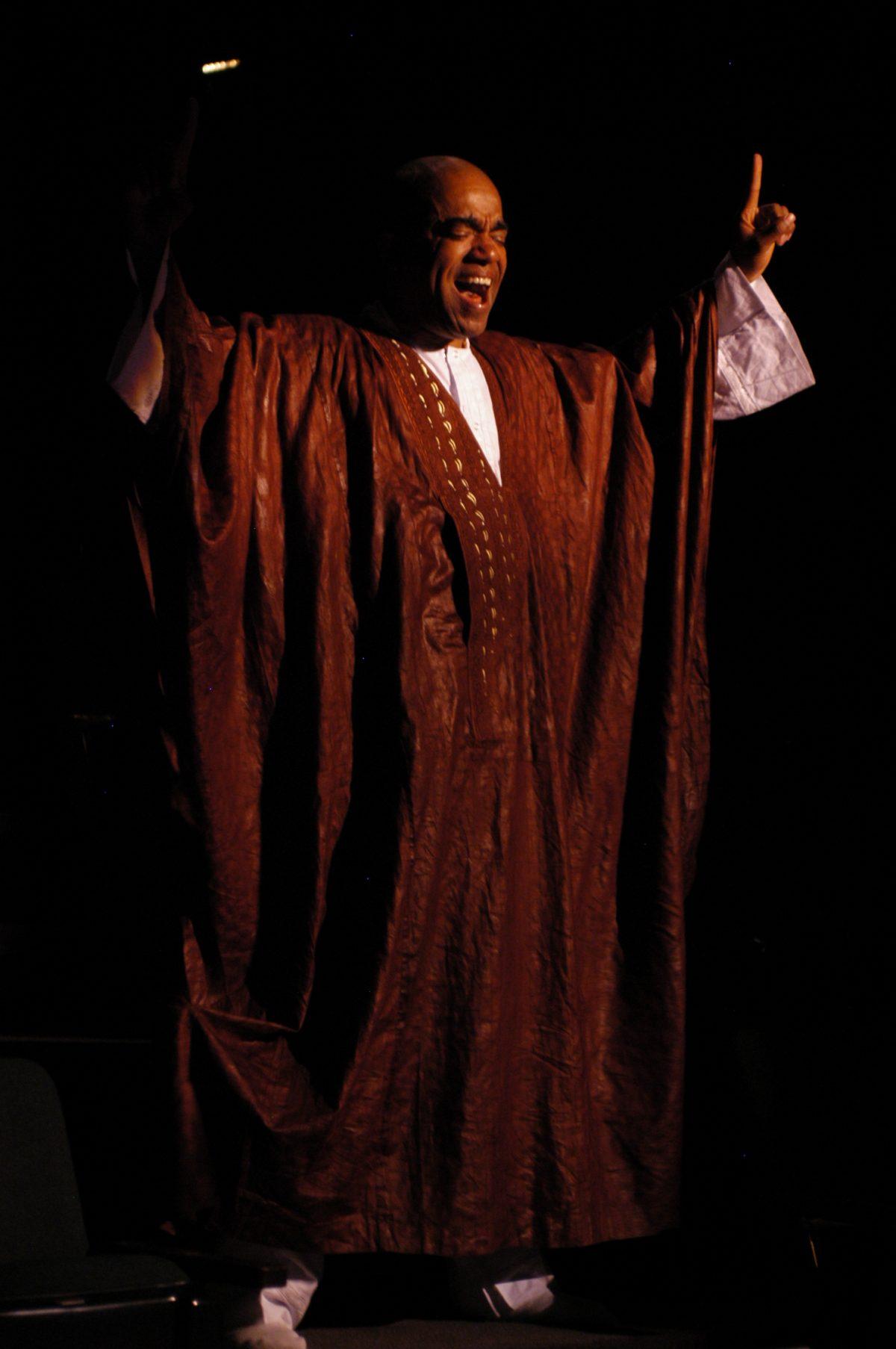 Man in brown robes singing.