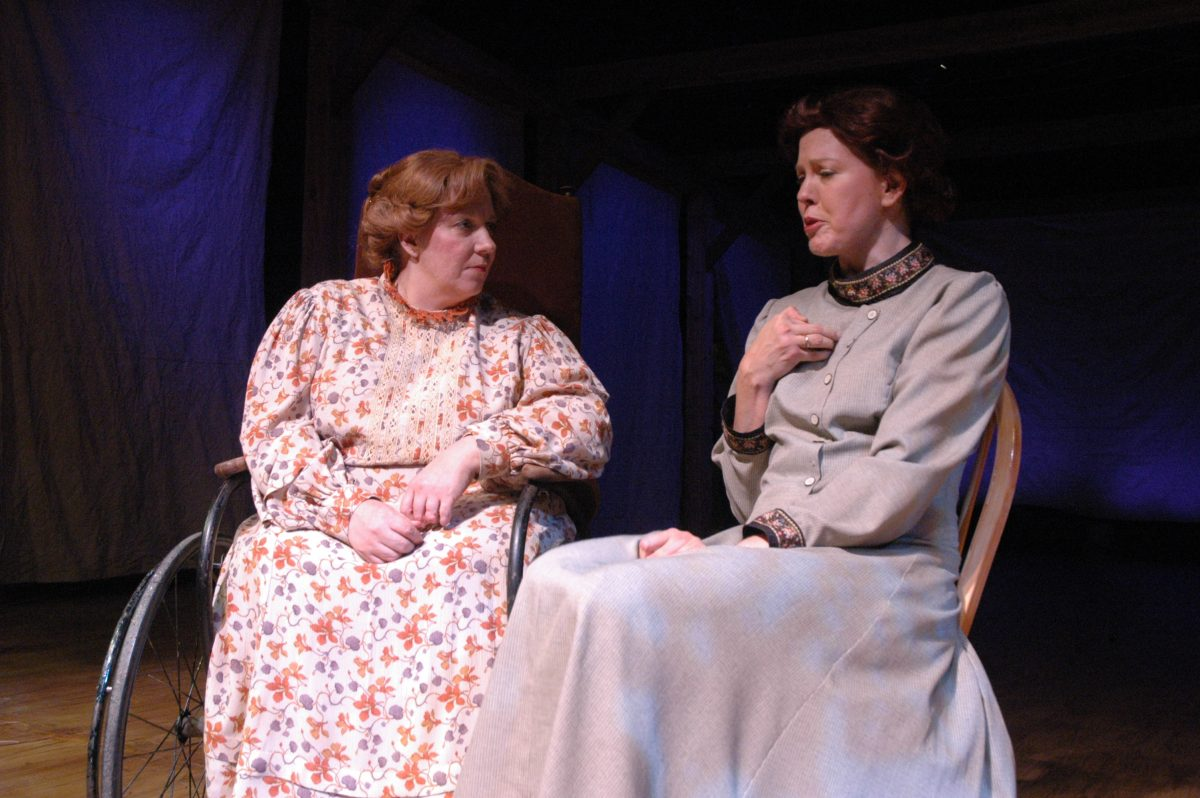 Woman wearing a long floral dress in a wheelchair sitting next to woman in long sleeve, high collared gray dress.