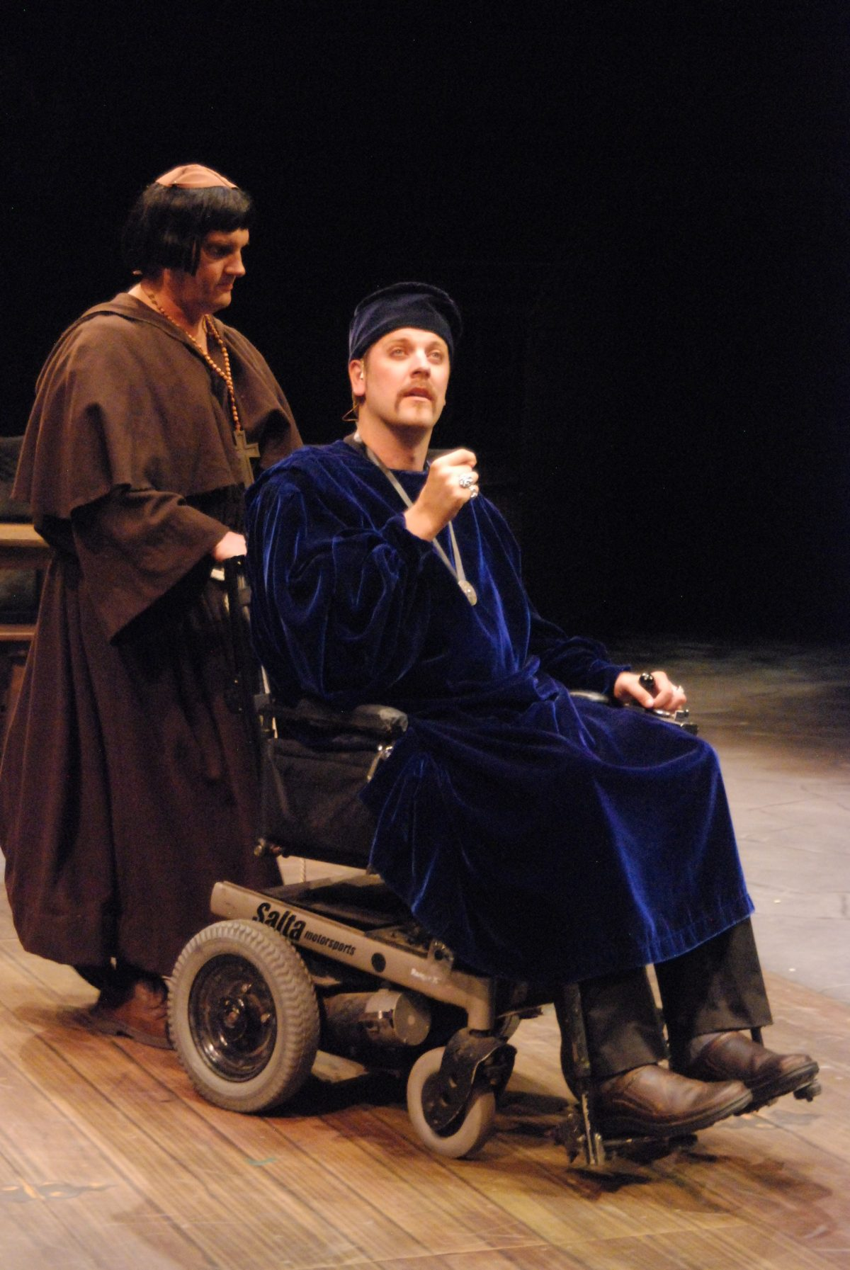Man in blue robes sitting in a wheelchair being pushed by man in monk's robe.
