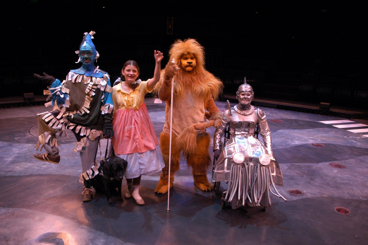 Four people in a line. One wearing scarecrow costume, then young girl with pigtails, then man in lion costume with white cane, then woman in wheelchair dressed in metallic costume.