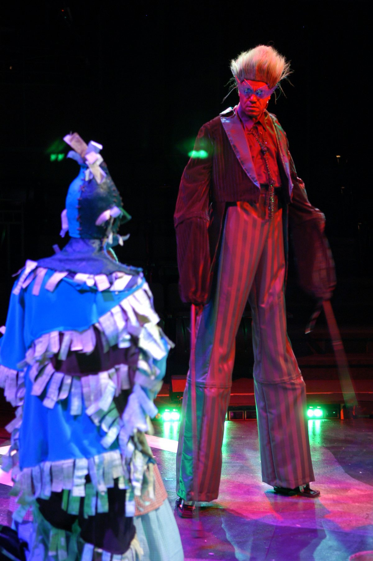 The back of a man in a scarecrow costume facing a man on stilts with striped pants goggles and hair that is sticking straight up.