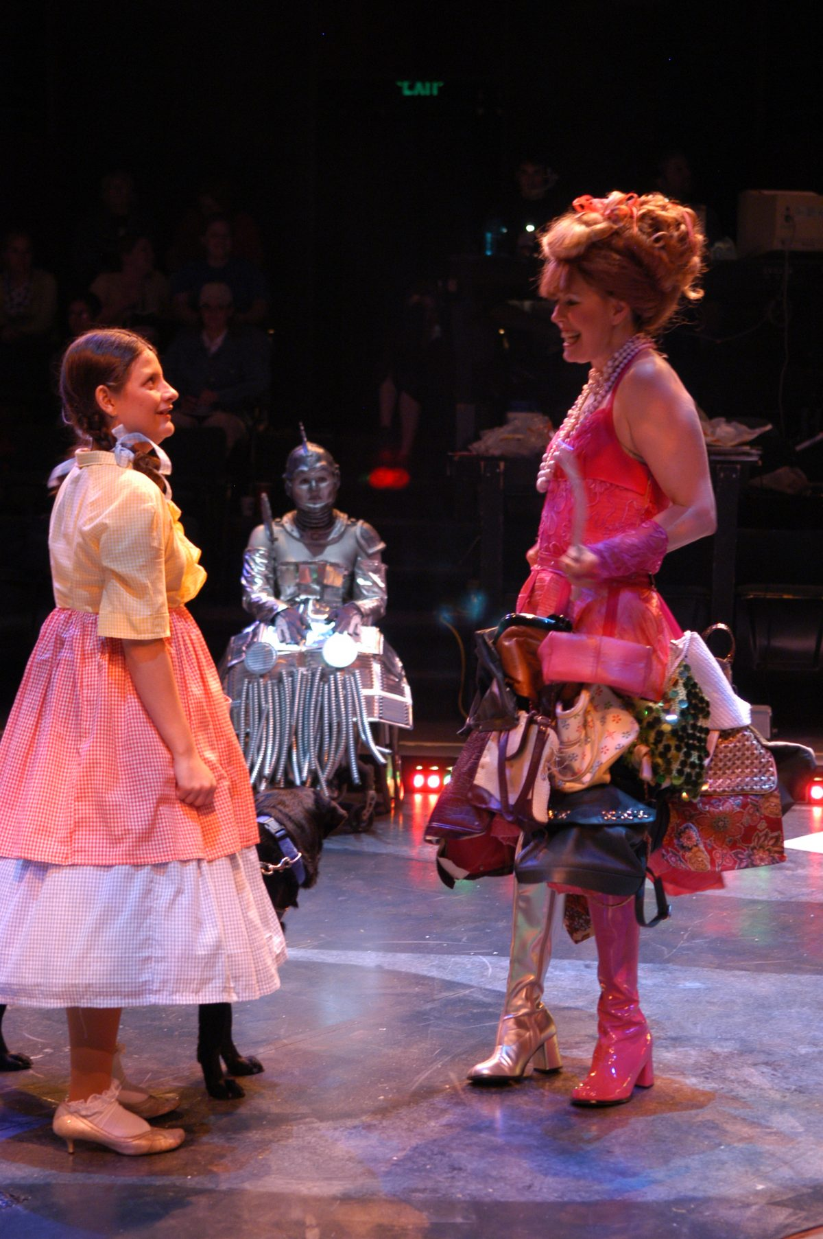 Girl with pigtails facing a woman in pink dress holding a wand. Woman in wheelchair and metallic costume in background.