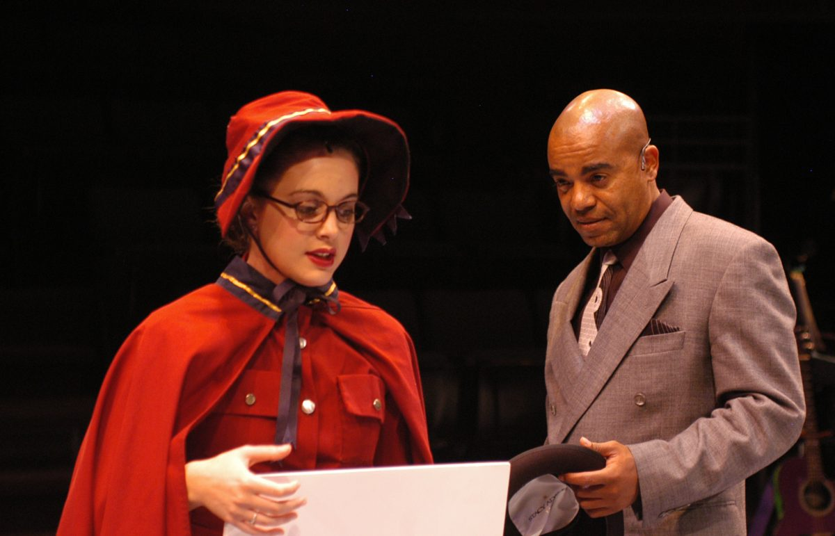 Woman in Red outfit and bonnet and Black bald man in suit looking down at paper