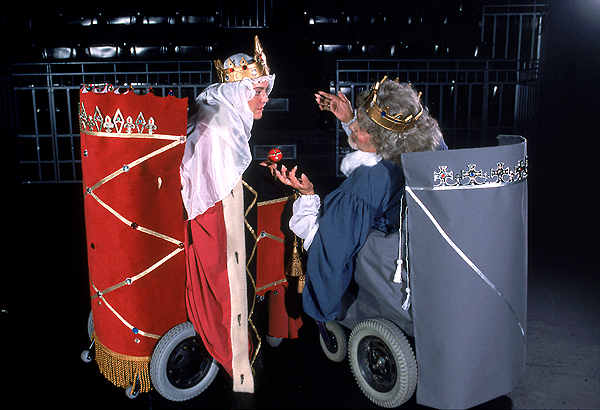 A woman and man both wearing crowns, in wheelchairs and facing the other direction.
