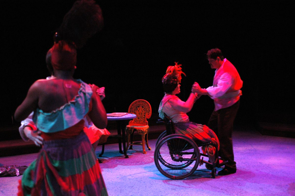Two couples dancing in colorful lights, one couple woman is in wheelchair.