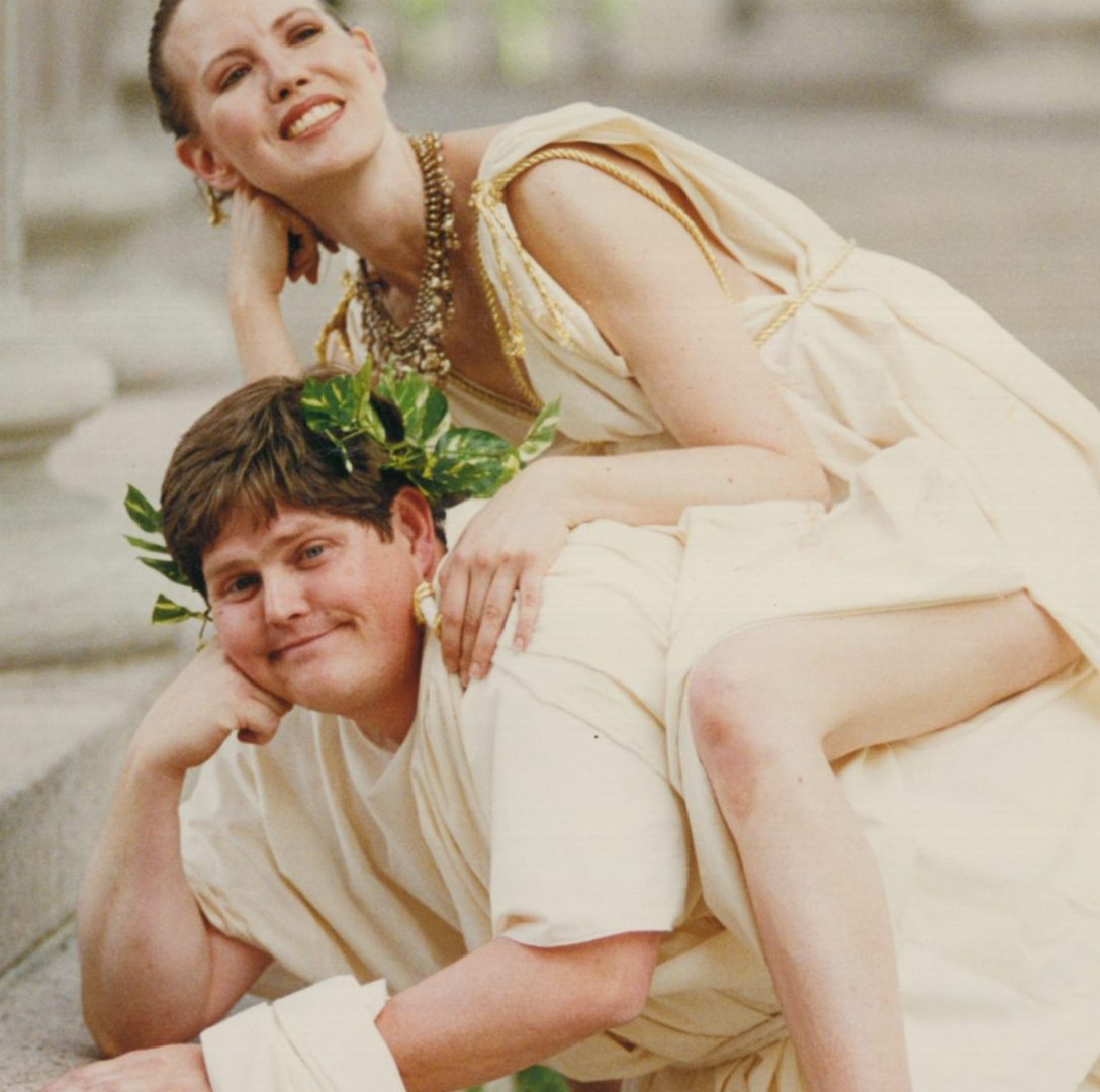 Man in toga with woman, also in toga, riding him piggy back