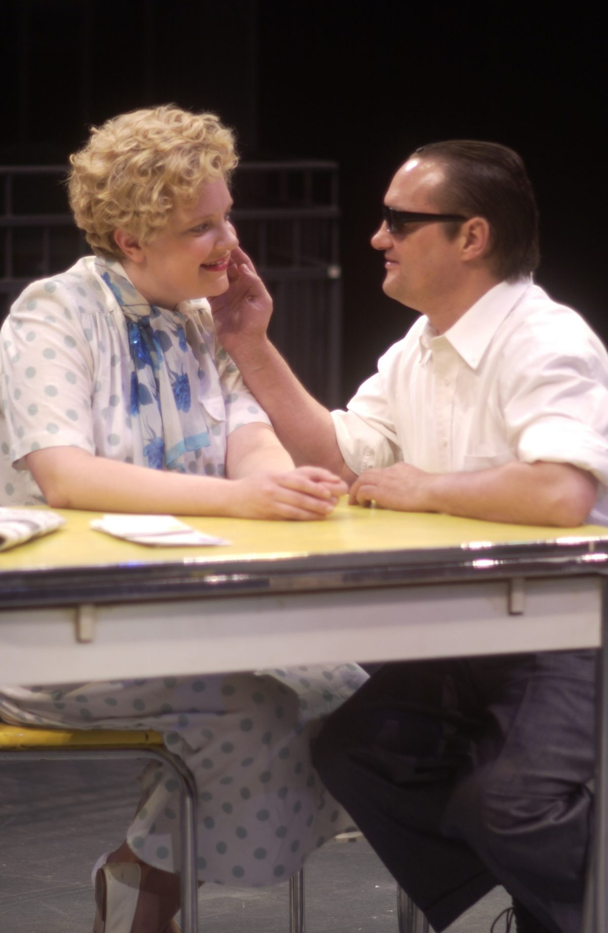 Woman in 50s dress sitting at a table, man with sunglasses sitting next to her touching her face.