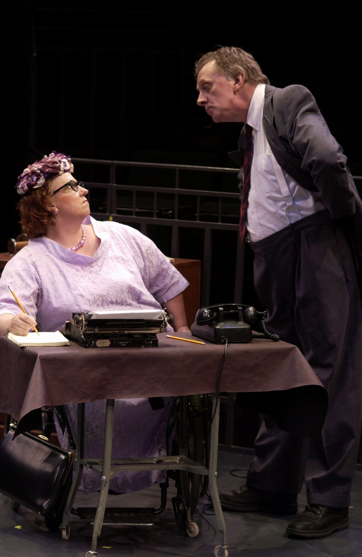 Woman at desk behind a typewriter with man in suit standing over her.